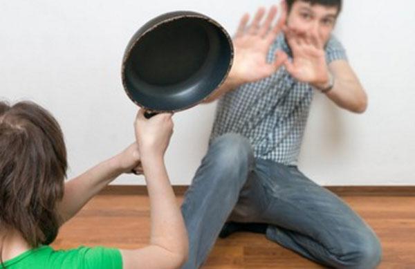 Перепуганный мужчина на полу. К нему подходит женщина со сковородой в руках