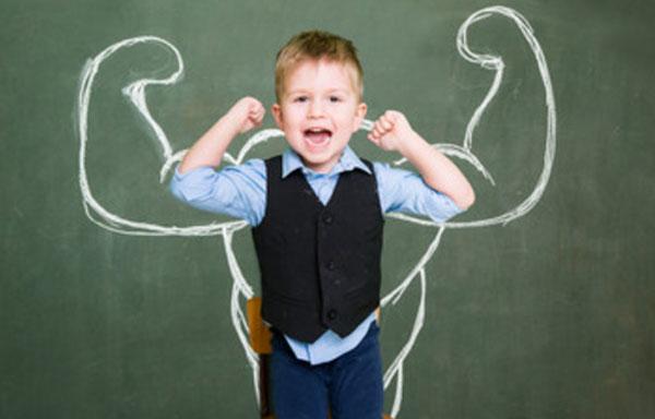 Мальчик стоит перед школьной доской, за ним нарисован силуэт мускулистого человека