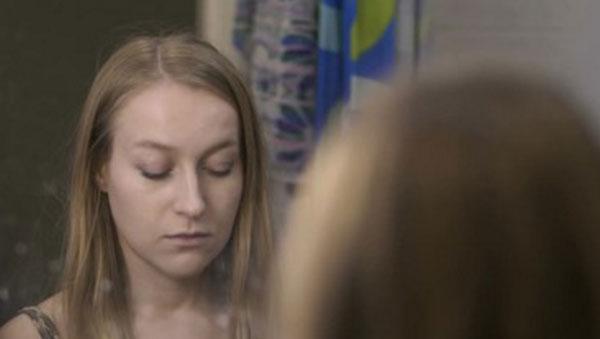 Одинокая девушка смотрит в зеркало с опущенными глазами