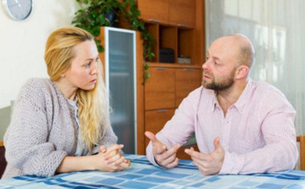 Пара с серьезными лицами общается за столом
