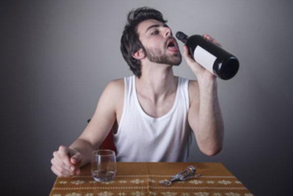 Мужчина пьет из горла бутылки