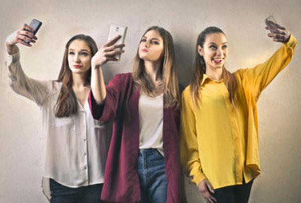 Три девушки делают селфи, каждая на своем телефоне