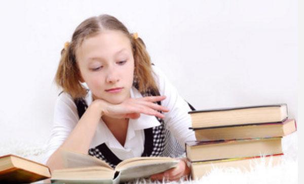 Девушка читает. На столе еще много книг