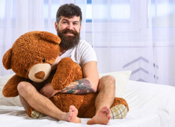 Инфантильный мужчина сидит на кровати, обнимая большую мягкую игрушку