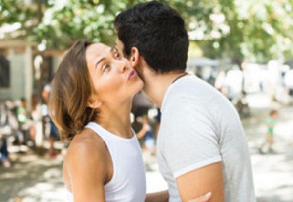 Девушка целует в щечку мужчину