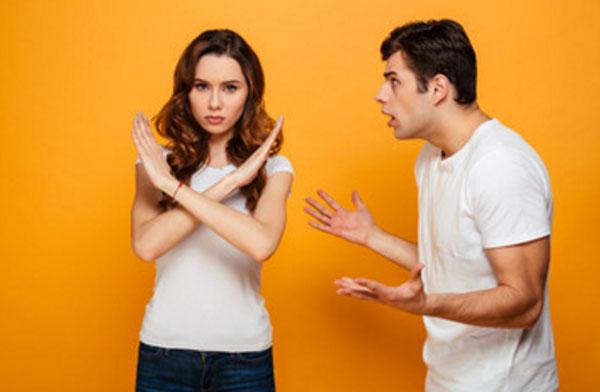 Парень что-то кричит на парня. Девушка стоит, скрестив руки