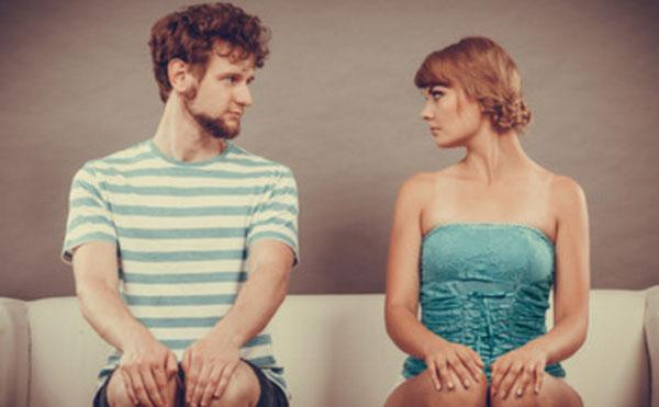 Девушка с парнем сидит на диване. Она серьезно и со злостью на него смотрит