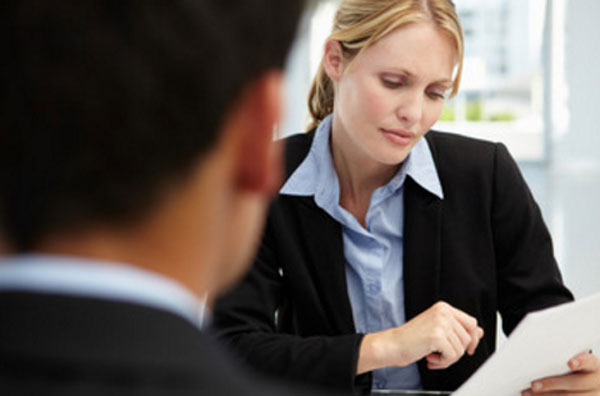 Девушка в костюме рассматривает заявление на листке бумаги