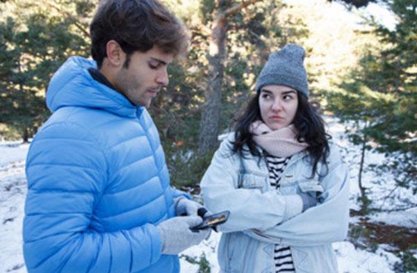 Парень копается в своем телефоне. Не смотрит на девушку, которая сильно замерзла и сердится