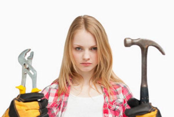Серьезная девушка. В руках мужские инструменты