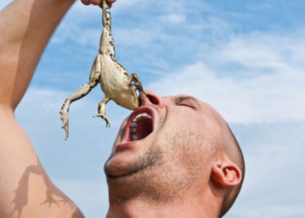 Мужчина тянет в рот живую лягушку