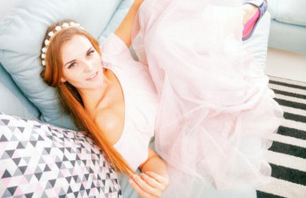 Девушка в красивом платье трогает свой локон