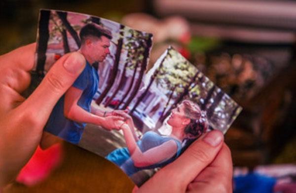 Девушка рвет фотографию, на которой она с парнем