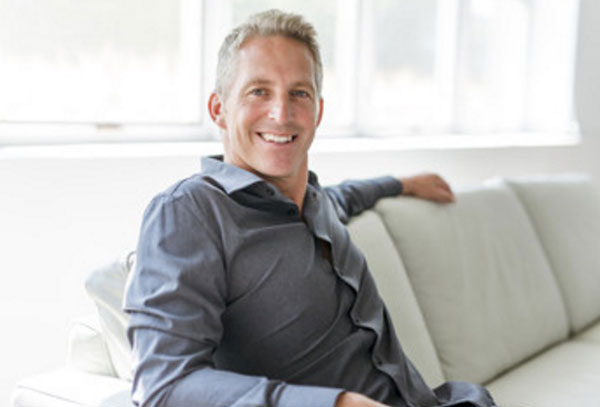 Красивый, улыбающийся мужчина 40 лет сидит на диване