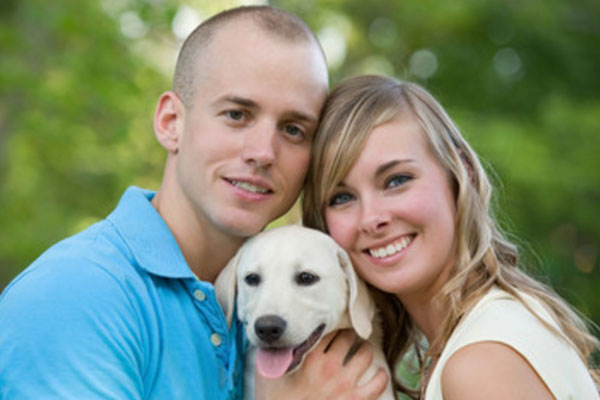 Счастливые парень и девушка, между ними щенок