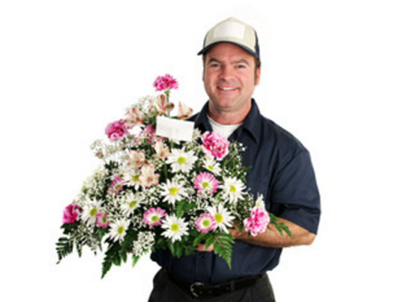 Улыбчивый курьер с букетом цветов, в который вставлена записка