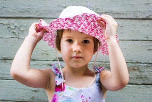 Девочка трех лет примеряет шляпку