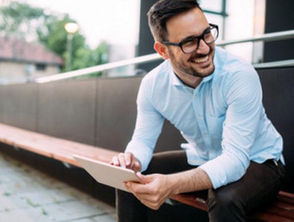Мужчина в очках сидит на улице и улыбается