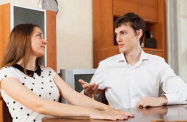 Парень разговаривает с девушкой, сидя за столом