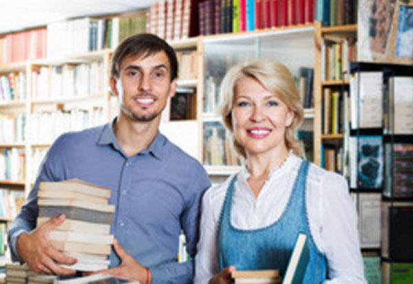 Зрелая женщина и молодой мужчина стоят в библиотеке с книгами в руках