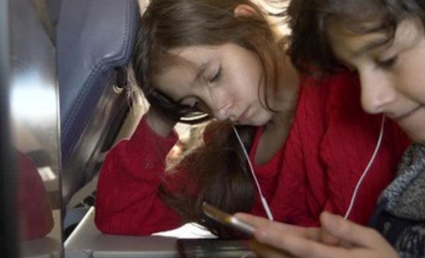 Дети в самолете, сидят в наушниках и что-то смотрят на телефоне и планшете