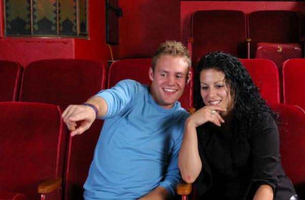 Парень с девушкой сидят рядом в театре и что-то обсуждают