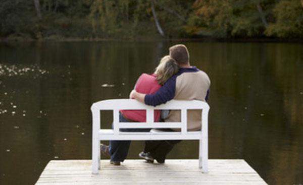 Влюбленная пара сидит на скамейке, на мостике, перед рекой