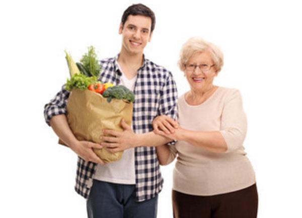 Парень несет покупки бабушки
