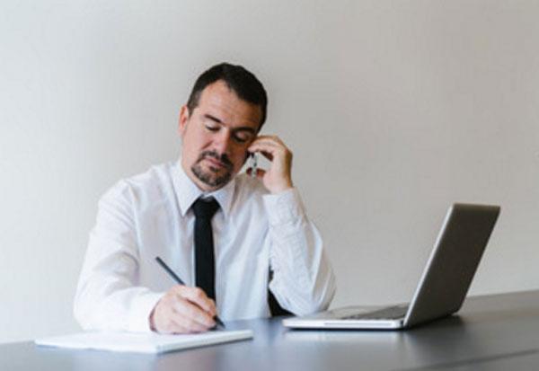 Мужчина работает. Перед ним ноутбук. Он что-то пишет и звонит по телефону