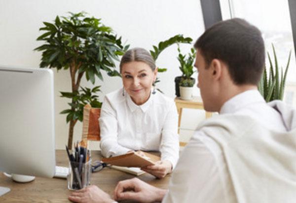 Зрелая женщина сидит за одним столом с молодым мужчиной