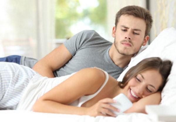 Парень с девушкой ляжат в постели. Девушка смотрит смс в телефоне и улыбается. Парень ревностно заглядывает, смотрит, что там в телефоне