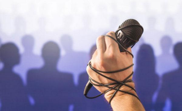 Рука, перевязанная проводом от микрофона. Сзади нее силуэты людей