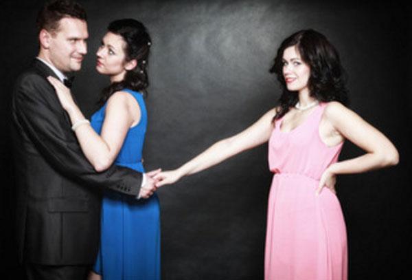 Мужчина обнимает женщину, а сам тянет руку другой. Женщина недовольна