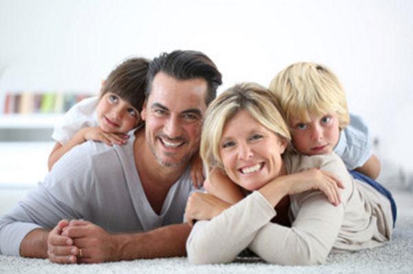 Счастливая семья из родителей и двух деток. Лежат на ковре и улыбаются