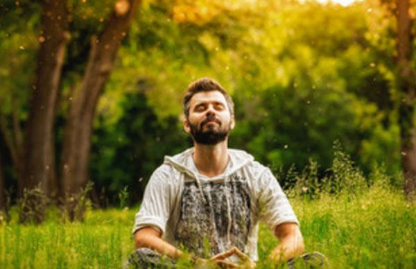 Мужчина сидит на траве и медитирует