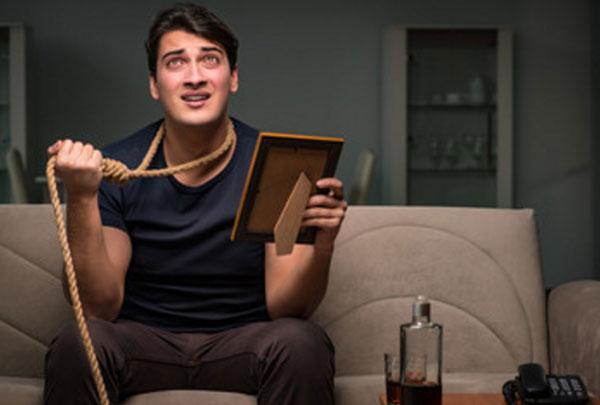 Мужчина с петлей на шее, держит в руке фото. На столе стоит алкоголь и телефон