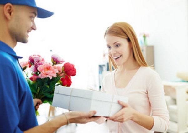 Курьер передает девушке коробку с подарком и цветы