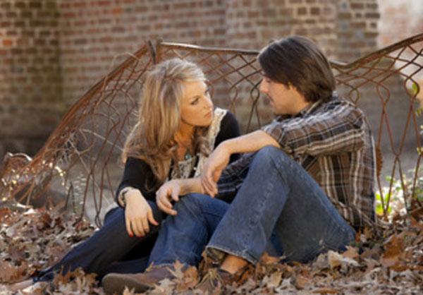 Парень с девушкой сидят в опавших листьях и серьезно разговаривают