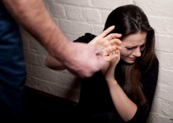 Женщина сидит на полу, пытается укрыться рукой от кулака мужа. Она вся в слезах