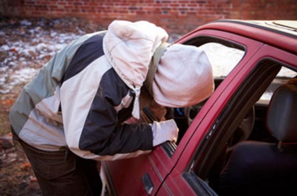 Подросток залез в окошко машины и пытается что-то украсть с переднего сидения
