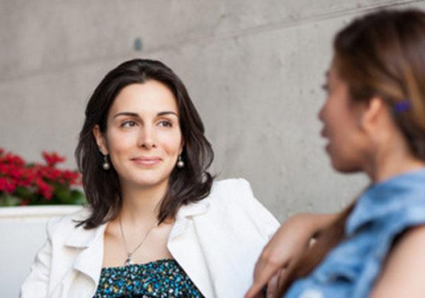 Женщины общаются. Одна мило улыбается