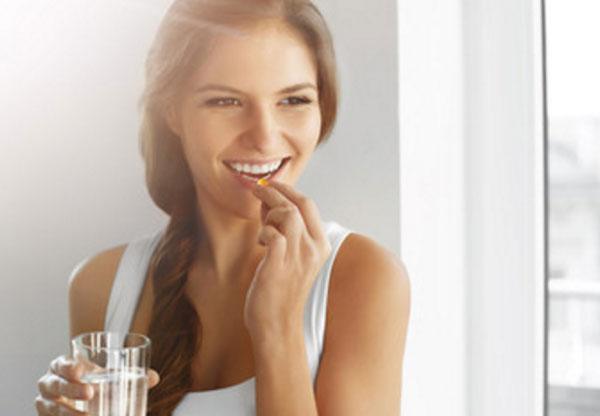 Девушка собирается выпить витаминку