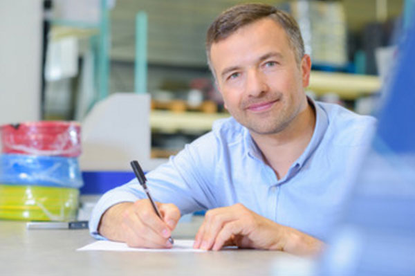 Мужчина что-то пишет на листке бумаги. Смотрит в камеру