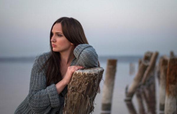 Девушка на реке стоит в задумчивости