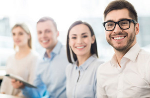 Четыре сотрудника сидят рядом, смотрят в камеру и улыбаются