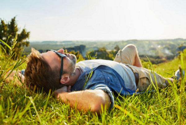 Спокойный и счастливый мужчина лежит на траве
