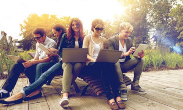 Студенты сидят на улице. Каждый зависает в ноутбуке или телефоне