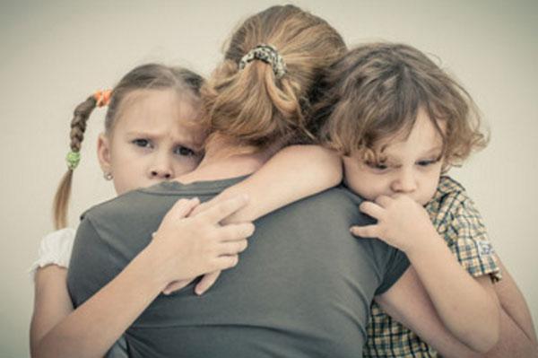 Женщина стоит спиной. Прижимает к себе сына и дочь. Дети недовольны