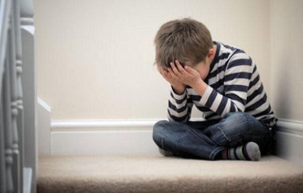Ребенок сидит возле ступенек и плачет