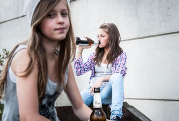 Две девочки сидят со спиртным, одна пьет с горла